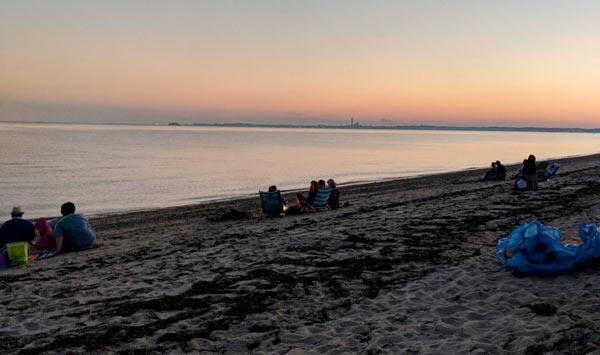 The sun sets over Cape Cod Bay in Truro, with the curve of Provincetown seen in the distance.